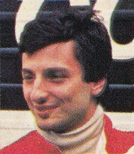 A man sporting black hair and wearing red racing overalls looking to the right of the camera