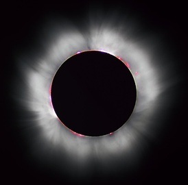 Totality during the 1999 solar eclipse. Solar prominences can be seen along the limb (in red) as well as extensive coronal filaments.