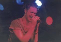 A male singer, Layne Staley, performs onstage with Alice in Chains. He holds the microphone with both hands and his eyes are closed as he sings.
