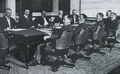 Negotiating the Treaty of Portsmouth (1905). From left to right: the Russians at far side of table are Korostovetz, Nabokov, Witte, Rosen, Plancon; and the Japanese at near side of table are Adachi, Ochiai, Komura, Takahira, Satō. The large conference table is today preserved at the Museum Meiji-mura in Inuyama, Aichi Prefecture, Japan.