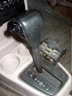 A floor selection lever in a 1992 Ford Escort showing the P-R-N-[D]-D-L modes as well as the shift lock button on the top of the lever