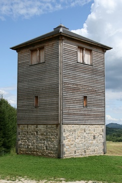 "Reconstruction of the specula or vigilarium (Germanic burgus), ""watchtower"", a type of castrum, at Rainau-Buch, Germany. An ancient watchtower would have been surrounded by wall and ditch.[14]"