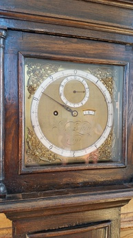 Photo of the face of the other surviving Sidereal Angle clock in the Royal Observatory in Greenwich, England, made by Thomas Tompion. The dial has been ornately inscribed with the name J Flamsteed, who was the Astronomer Royal, and the date 1691.