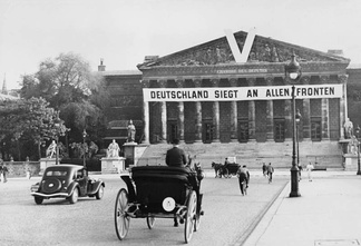 "A German propaganda banner on the Palais Bourbon in July 1941. It reads ""Germany is victorious on all fronts""."