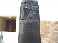 Detail from Hammurabi's stele shows him receiving the laws of Babylon from the seated sun deity.