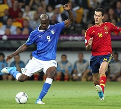 Spain holding midfielder Sergio Busquets (16, red) moves to block a shot from Mario Balotelli.