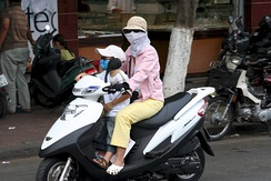 "A woman rider and her child with hidden face in Ho Chi Minh City, a common street culture practised among southern Vietnamese women due to the annual hot season in the south which frequently dubbed as the Vietnamese version of ""women ninja"".[284]"