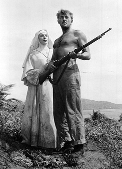 Black and white photo of Robert Mitchum holding a gun standing next to Deborah Kerr in the movie Heaven Knows Mr. Allison in 1957