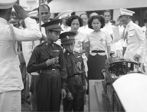 Thirteen year old King Ananda of Siam (left), and his brother Prince Bhumibol Adulyadej (right), inspect a model train presented to him at Saranrom Park in Bangkok in 1938.