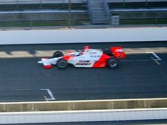 "Hélio Castroneves makes his pole-winning qualification run in 2007 during ""Happy Hour"". Note the shadows cast on the racing surface."