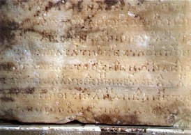 A photograph of the original stone at Delphi containing the second of the two Delphic Hymns to Apollo. The music notation is the line of occasional symbols above the main, uninterrupted line of Greek lettering.