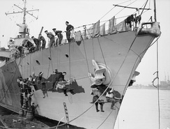 Members of the crew of Fantasque-class destroyer Le Triomphant in working rig, seated on gantries hanging over the ship's side, painting the ship's bow. Le Triomphant was one of the French naval ships that came to British ports after the fall of France and was crewed by Free French sailors, forming part of the Free French Navy. 1940