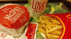 "A typical ""eat-in"" McDonald's meal as sold in Hong Kong, consisting of French fries, a soft drink, and a ""main product"" – in this case, a McSpicy Chicken Fillet. Condiments are supplied in small packets; such a packet of tomato ketchup is seen in the foreground."