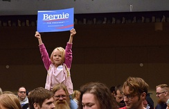 "Five-year-old Courtney Skinner holds up a ""Bernie Sanders for President"" sign while sitting on Tom Skinner's shoulders at the Juneau Democratic Caucus on Saturday, March 26, 2016 in Centennial Hall's Sheffield Ballroom. Sanders won the majority of Juneau's votes and those across Alaska. (James Brooks photo)"