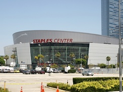 "A white round building that has one glass front wall showing with a sign in red text that reads ""Staples Center"" in capital letters. In the background, there are multiple people waling in front of the building and a white parked car and a cloudy blue sky."