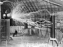 "Serbian-American inventor Nikola Tesla sitting in the Colorado Springs experimental station with his ""Magnifying transmitter"" generating millions of volts."