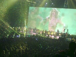An image of a woman dancing is being projected onto a large screen. There is green lighting in the entire arena and large amounts of confetti are floating in the air.