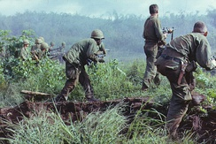 An infantry patrol moves up to assault the last Viet Cong position at Dak To, South Vietnam after an attempted overrun of the artillery position by the Viet Cong during Operation Hawthorne