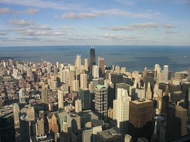 View of downtown Chicago, seen from the Willis Tower. The tall, black building in the center of the image is the John Hancock Center, and Lake Michigan is in the background.