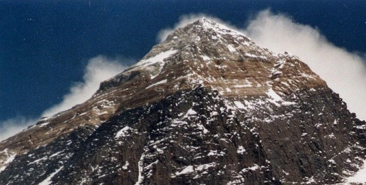 Mount Everest with snow melted, showing upper geologic layers in bands.