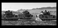 Three M2A3 Bradleys exit an OCCD at the start of a Patrol at Fort Irwin, California.