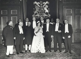 A formal group of Elizabeth in tiara and evening dress with eleven politicians in evening dress or national costume.