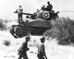 An American crew checks their Sherman tank after landing at Red Beach 2, Sicily, 10 July.