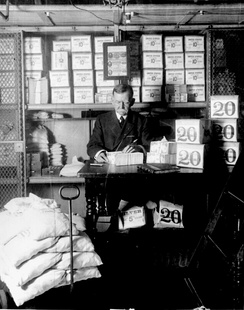 Treasury Department official, surrounded by packages of newly minted currency, counting and wrapping dollar bills. Washington, D.C., 1907.