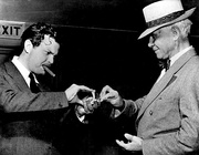 Welles performs a card trick for Carl Sandburg before the War Bond drive broadcast I Pledge America (August 1942).