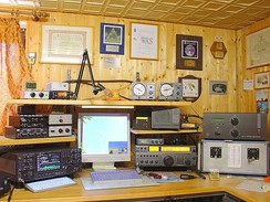 An example of an amateur radio station with four transceivers, amplifiers, and a computer for logging and for digital modes. On the wall are examples of various amateur radio awards, certificates, and a reception report card (QSL card) from a foreign amateur station.