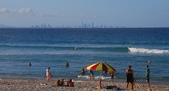 A Queensland beach with the skyline of the heavily developed Gold Coast in the background. Formerly swamplands, the city was urbanised on a coastal strip between waterways and the sea and now contains many high rises.
