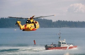 A Canadian Forces CH-149 Cormorant helicopter hoists a man from a Canadian Coast Guard cutter