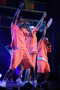 Three men performing on stage with upraised arms, wearing matching neon-orange shorts and polo shirts