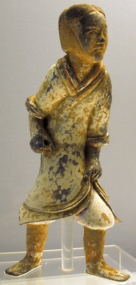 A Han dynasty era pottery soldier, with a now-faded coating of paint, is missing a weapon.
