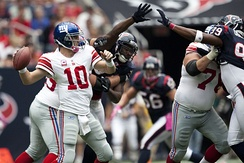 Eli Manning lines up a pass just out of the reach of Houston Texans defenders in 2010.
