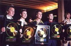 Boy band Plus One displaying their gold records