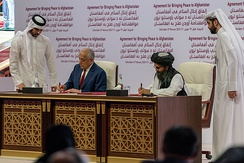 US representative Zalmay Khalilzad (left) and Taliban representative Abdul Ghani Baradar (right) sign the Agreement for Bringing Peace to Afghanistan in Doha, Qatar on 29 February 2020
