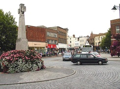 Street scene showing roads and shops around a stone cross.