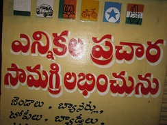 Wall painting at a shop in India. It first shows the painted party symbols of all the major political parties in the region during the nationwide elections in India in 2014. It also has a Telugu inscription showing availability of political flags, banners, caps, badges and other election material.