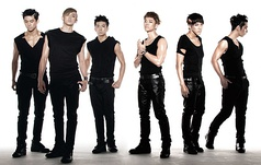 Six men wearing form-fitting black sleeveless shirts, leather pants, and combat boots. They have prominent eye makeup and each has a different gelled hairstyle.