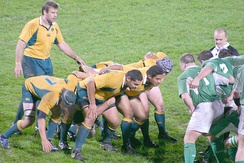 A scrum is preparing to engage. The front row consists of two props on either side of the hooker. The number eight can be seen standing up at the back, while the flankers are bound on the side.