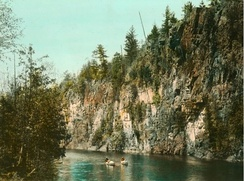 A hand-coloured photograph of canoeists in Algonquin Park in the 1920s