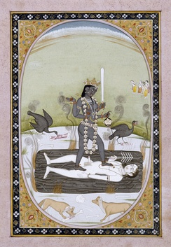 A Kangra painting of Kali stands on Shiva, who assumes the position of a corpse atop a blazing funeral pyre. Dogs and scavenger birds surround Kali.