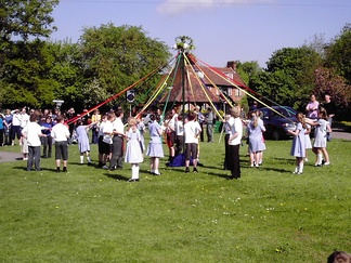 Children dancing around a maypole as part of a May Day celebration in Welwyn, England
