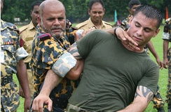 A Bangladesh Rifles Senior Warrant Officer (left in yellow/green outfit) applies a mechanical advantage control/hold to a US Marine during training.