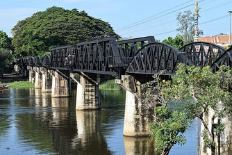 The River Kwai railroad bridge in 2017. The arched sections are original (constructed by Japan during WWII); the two sections with trapezoidal trusses were built by Japan after the war as war reparations, replacing sections destroyed by Allied aircraft.