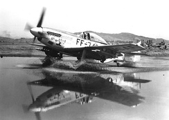 F-51 Mustang, laden with bombs and rockets, taxis through a puddle at an airbase in Korea.