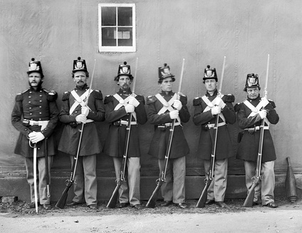 Five U.S. Marine Corps privates with fixed bayonets under the command of their noncommissioned officer, who displays his M1859 Marine NCO sword.