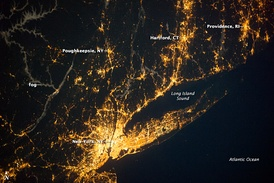 Satellite imagery showing the New York metropolitan area at night. Long Island extends to the east of the central core of Manhattan.