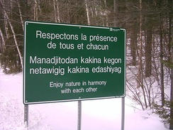 "Sign at La Vérendrye Wildlife Reserve in French, Algonquin and English. The Algonquin text ""Manàdjitòdan kakina kegòn netàwigig kakina e-dashiyag"" literally translates to ""Be gentle with all things of nature for everyone."""